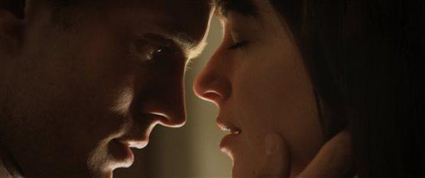 """En esta imagen difundida por Universal Pictures y Focus Features, Jamie Dornan, a la izquierda, y Dakota Johnson en una escena de """"Cincuenta sombras de Grey"""", que se estrena el 14 de febrero del 2015. (AP Foto/Universal Pictures y Focus Features)"""