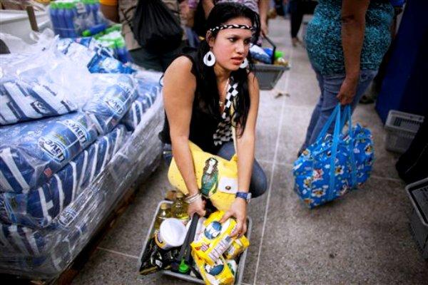 Una mujer espera en una cola para pagar en la caja en el supermercado Día a Día en el barrio Propatria de Caracas, Venezuela, el martes 3 de febrero de 2015. El gobierno está ocupando de manera temporal la cadena de supermercados Día a Día como parte de una ofensiva en contra de las empresas privadas a las que culpa de un empeoramiento en la escasez de bienes básicos y de las largas colas. Entre los bienes, cuyos precios son controlados por el gobierno, y que no se consiguen fácilmente están el café, el aceite de cocina, la harina de maíz, el azúcar, la leche, el papel higiénico, los pañales desechables, detergentes y suavizantes para ropa, entre otros artículos. (AP Foto/Ariana Cubillos)
