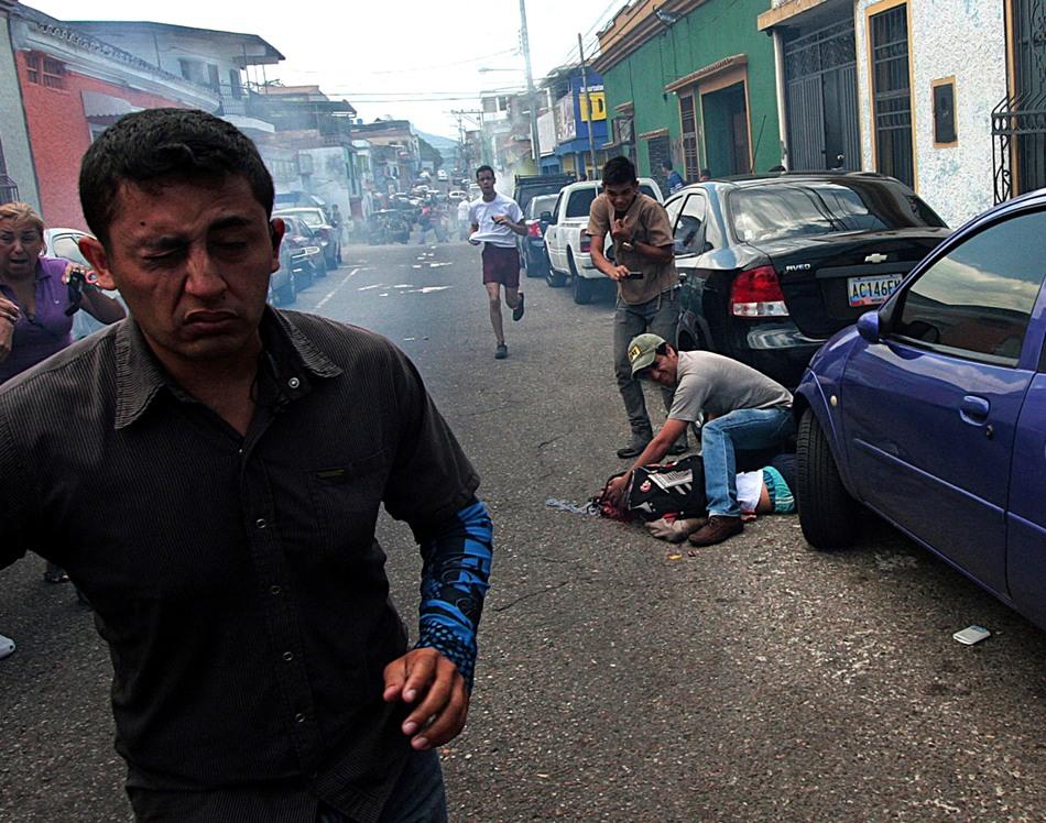 Un hombre asiste a un joven herido durante una protesta contra el gobierno de Nicolás Maduro en San Cristóbal, Venezuela, el martes 24 de febrero de 2015. El joven de 14 años identificado como Kluiverth Roa, según el concejal de esa localidad José Vicente García, recibió un disparo en la cabeza durante enfrentamientos entre los manifestantes y la policía, que intentaba dispersarlos. Murió camino al hospital. (Foto AP)