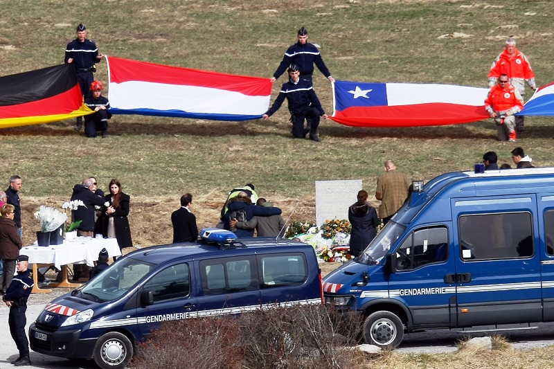 Banderas representando las nacionalidades de los fallecidos en el accidente del vuelo de Germanwings en Los Alpes, desplegadas durante una cerremonia de homenaje con familiares de las víctimas ante un monolito en su memoria, en Le Vernet, Francia, el 29 de marzo de 2015. (Foto AP/Claude Paris)