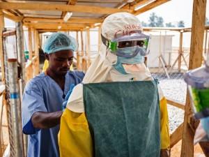 Un empleado sanitario prepara la ropa protectora de un colega antes de ingresar a una zona de alto riesgo en una clínica para pacientes con ébola en Makeni, Sierra Leona. (Foto AP/Michael Duff)