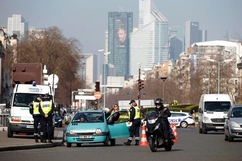 Policías verifican un auto en París, Francia, el lunes 23 de marzo de 2015. Las autoridades parisinas prohibieron el lunes la circulación de vehículos con placas nones en un intento por reducir la contaminación en la capital francesa. (Foto AP/Francois Mori)