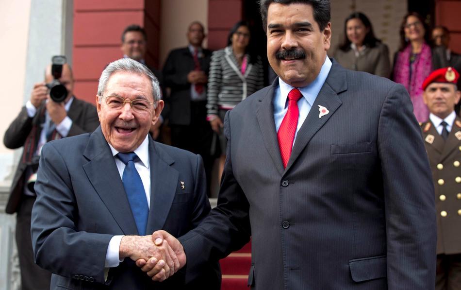 El presidente de Cuba Raúl Castro, izquierda, se saluda con el gobernante venezolano Nicolás Maduro frente a la prensa después de llegar al palacio presidencial de Miraflores para una reunión de emergencia del ALBA en Caracas, Venezuela, el martes 17 de marzo de 2015.  (AP Photo/Ariana Cubillos)