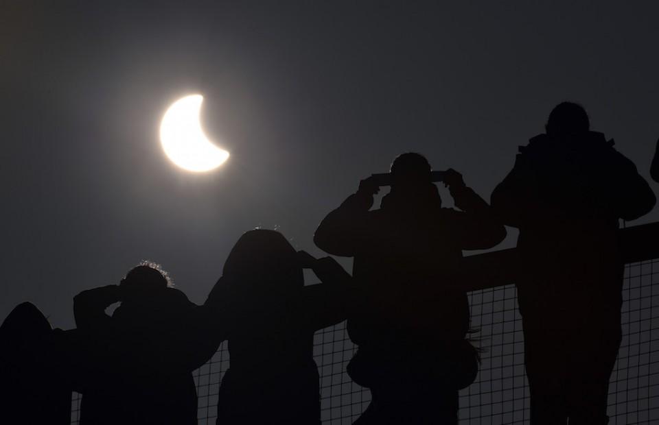 Gente mirando el comienzo de un eclipse solarsobre el Eden Project, cerca de St Austell, en Cornualles, Inglaterra, el 20 de marzo de 2015.  (AP Foto/PA, Ben Birchall)