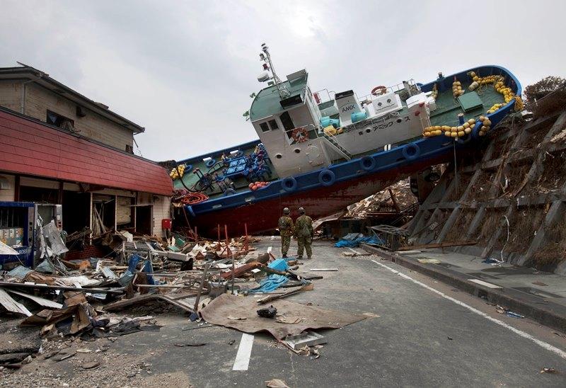 dos soldados japoneses se detienen para mirar un barco bloqueando una calle en la ciudad de Onagawa