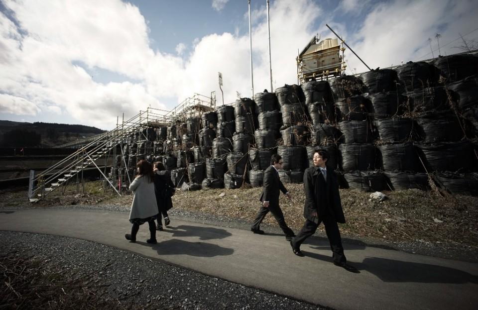 En esta imagen del 4 de marzo de 2015, gente caminando junto a un dique temporal en una zona dañada por el tsunami en Rikuzentakata, en la prefectura de Iwate, en el nordeste de Japón. Aún luchando por recuperarse, la zona golpeada por el tsunami en el noroeste de Japón, conmemoró el cuarto aniversario del desastre el 11 de marzo de 2015. (AP Foto/Eugene Hoshiko)