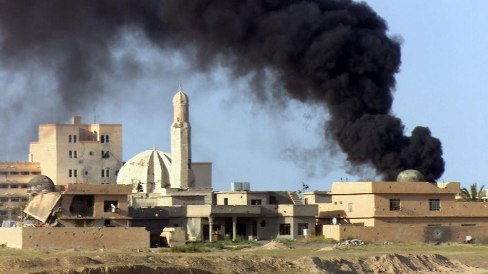 Una cortina de humo se eleva entre los edificios durante enfrentamientos entre el ejército iraquí y el grupo Estado Islámico (EI) en Tikrit, Irak, hoy, 31 de marzo de 2015.  EFE/STR