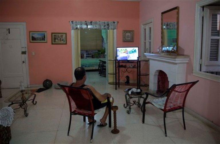 Un propietario, sentado en la sala de estar de su casa con habitaciones para alquinar en La Habana, Cuba, el 1 de abril de 2015. (Foto AP/Desmond Boylan)