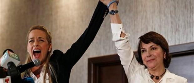 """Lilian Tintori, esposa del encarcelado opositor venezolano Leopoldo López, izquierda, grita """"Libertad"""" acompañada de Mitzy Capriles de Ledezma, esposa del también encarcelado alcalde de Caracas Antonio Ledezma, en una rueda de prensa en Ciudad de Panamá, el jueves 9 de abril de 2015. Ambas criticaron al gobierno de Venezuela el día previo a la Cumbre de las Américas.(AP Photo/Arnulfo Franco)"""