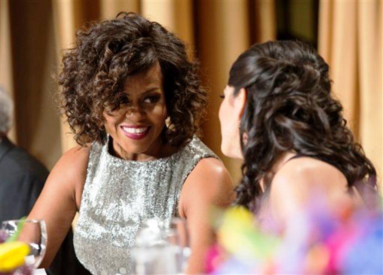 La primera dama de Estados Unidos, Michelle Obama, charla con una asistente a la cena benéfica anual de la Asociación de Corresponsales de la Casa Blanca en el hotel Hilton de Washington, el 25 de abril de 2015, en Washington. (Foto AP/Evan Vucci)