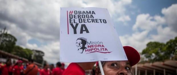 """Una mujer sostiene un afiche de protesta contra el decreto del presidente de EE.UU., Barack Obama, que considera a Venezuela una """"inusual y extraordinaria amenaza"""" para la seguridad estadounidense, hoy, martes 31 de marzo de 2015, durante una manifestación en Caracas (Venezuela). EFE/Miguel Gutiérrez"""