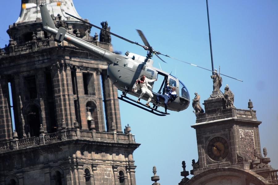 """Un extra realiza acrobacias en un helicóptero sobre el Zócalo de la Ciudad de México durante la filmación de """"Spectre"""" la más reciente película de James Bond en México, el lunes 30 de marzo de 2015. El gobierno de la Ciudad de México aseguró el jueves 2 de abril que la filmación de """"Spectre"""", en el corazón de su centro histórico fue benéfica para la actividad económica local. (Foto AP/Sandra Stargardter)"""