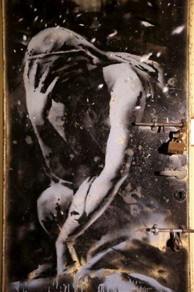 Una puerta de metal que muestra a una diosa griega, supuestamente pintados por el artista británico Banksy, que estaba entre los escombros de un edificio dañado en la guerra entre Israel y Hamas del verano pasado, al este de Yebaliya.  (AP Foto/Adel Hana)