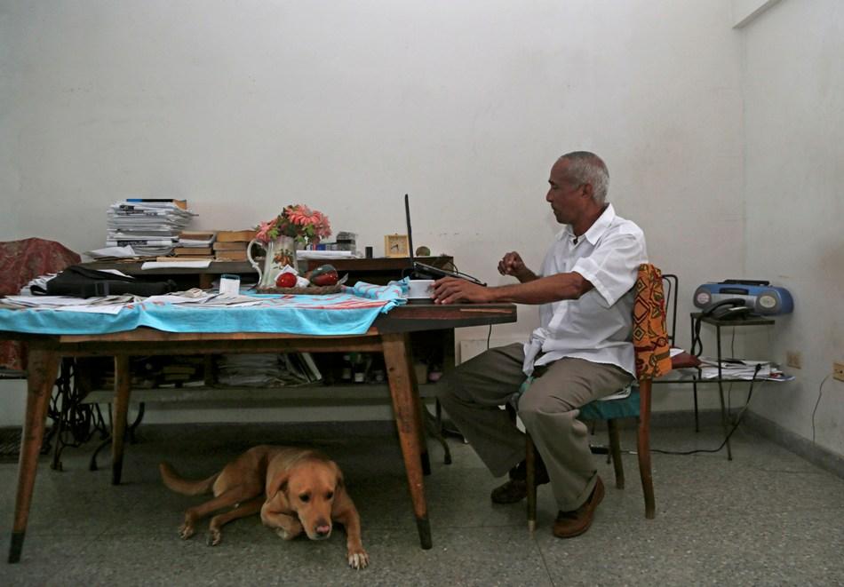 En esta imagen del 16 de abril de 2015, el disidente cubano Hildebrando Chaviano trabaja en su computadora portátil en su casa de La Habana.  (Foto AP/Desmond Boylan)