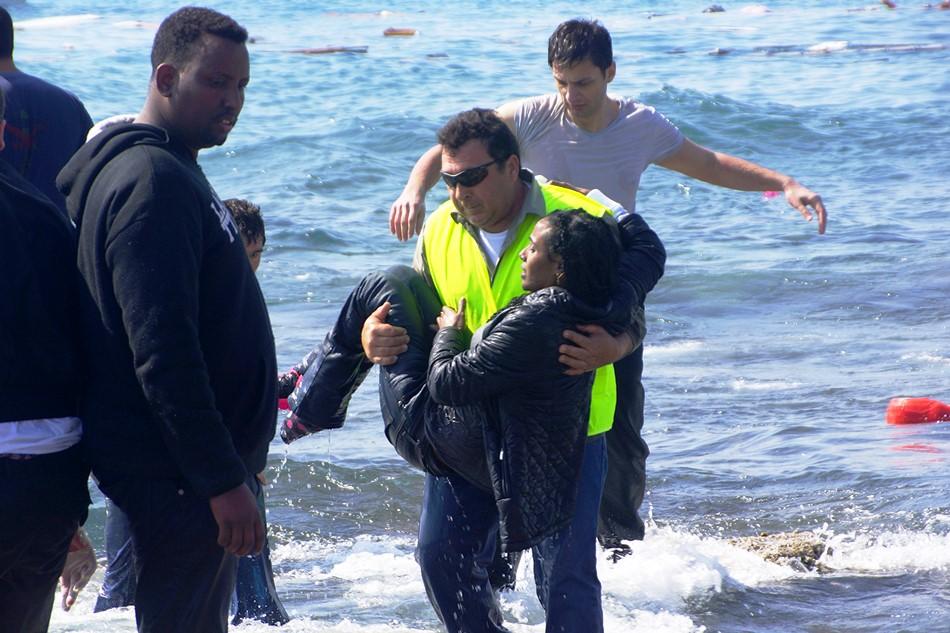 Un hombre rescata a una migrante en el Mar Egeo, en la Isla de Roda, Hrecia, el lines 20 de abril de 2015. Autoridades griegas dijeron qu al menos tres personas han fallecido cuando un barco de madera que llevaba a decenas de migrantes encalló frente a la isla. (Argiris Mantikos/Eurokinissi vía AP)