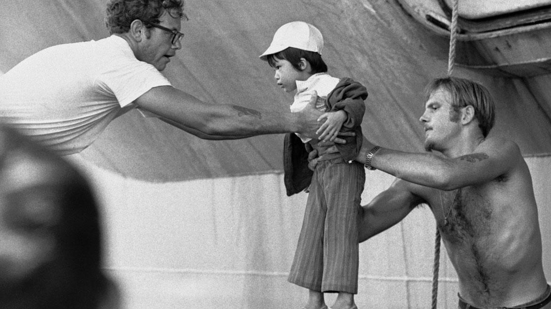 Evacuación de Vietnam del Sur: Marinos norteamericanos trasladan a un niño vietnamita a una embarcación local en 1975. AP