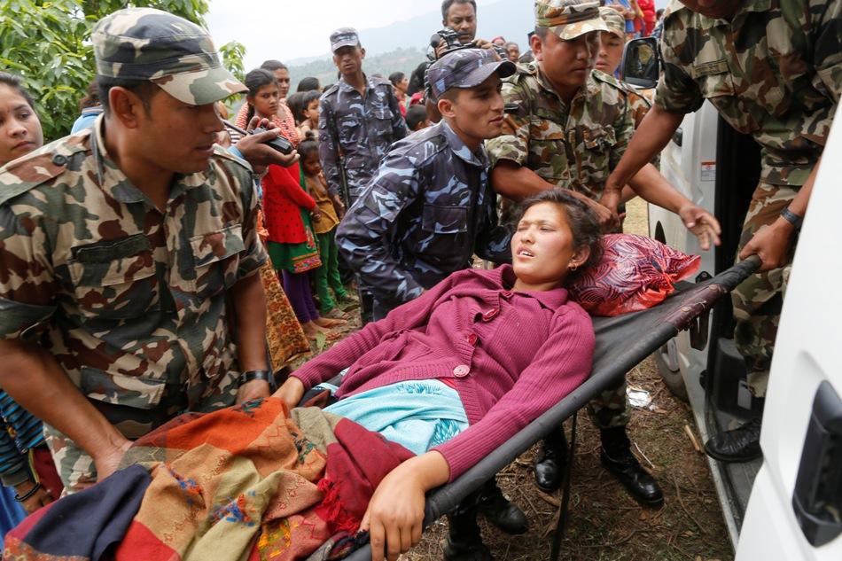 Sita Karka, con dos piernas rotas luego del sismo del pasado sábado en Pakistán, es trasladada a una ambulancia por soldados y policías nepalíes tras ser evacuada en helicoptero desde su aldea, Ranachour, muy afectada por el temblor, en la localidad de Gorkha, Nepal, el 28 de abril de 2015. (Foto AP/Wally Santana)