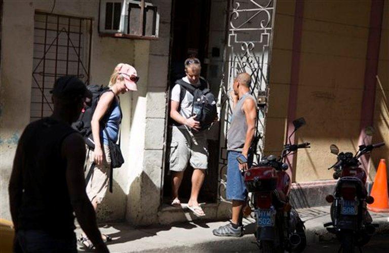 Un turista sale de una vivienda particular con habitaciones para alquilar en La Habana, Cuba, el 1 de abril de 2015. El enormemente popular servicio en línea Airbnb para renta de viviendas permitirá a los viajeros estadounidenses reservar alojamiento en Cuba a partir del jueves, la más significativa expansión empresarial de Estados Unidos en la isla desde que a fines del año pasado se anunció que ambos países reanudarían sus relaciones.(Foto AP/Desmond Boylan)