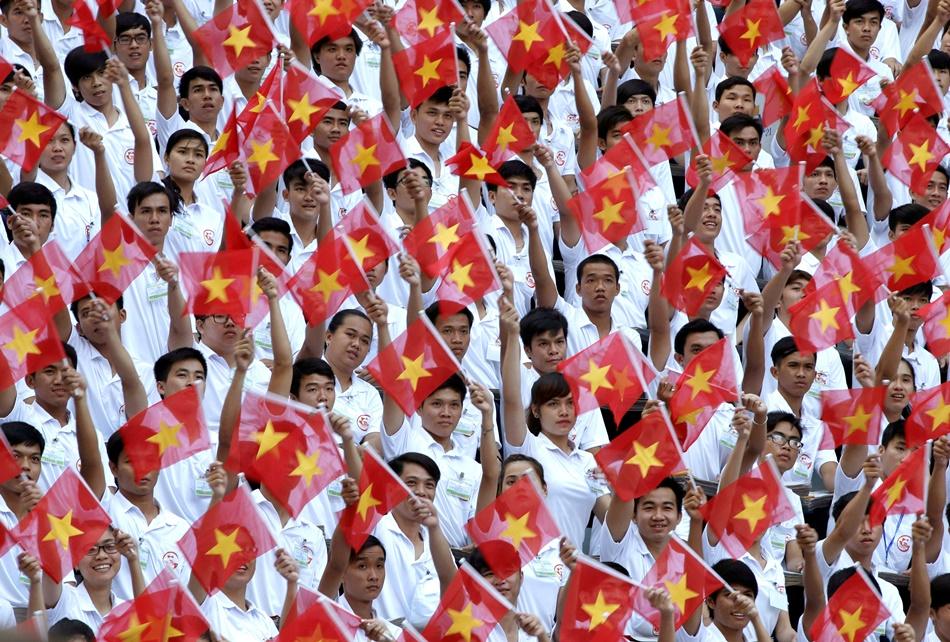 """Participantes en un desfile ondean la bandera nacional de Vietnam durante la celebración del 40 aniversario del final de la guerra de Vietnam, recordada también como la """"caída de Saigón"""", en Ho Chi Minh, Vietnam, el 30 de abril de 2015. (Foto AP/Dita Alangkara)"""