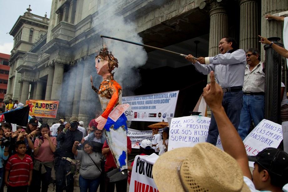 Un hombre sostiene una efigie de la vicepresidenta guatemalteca Roxana Baldetti mientras se quema durante la marcha por el Día del Trabajo, frente al Palacio Nacional en Ciudad de Guatemala, el viernes 1 de mayo de 2015. Trabajadores sindicalizados se reunieron para protestar contra el reciente escándalo de corrupción que involucra al secretario particular de Baldetti, al que las autoridades han identificado como el presunto cabecilla de una organización dedicada a defraudar al estado a través de la corrupción y el robo. El sábado 2 de mayo, miles de guatemaltecos salieron por segunda ocasión a protestar para exigir la renuncia de Baldetti. (Foto AP/Moisés Castillo)