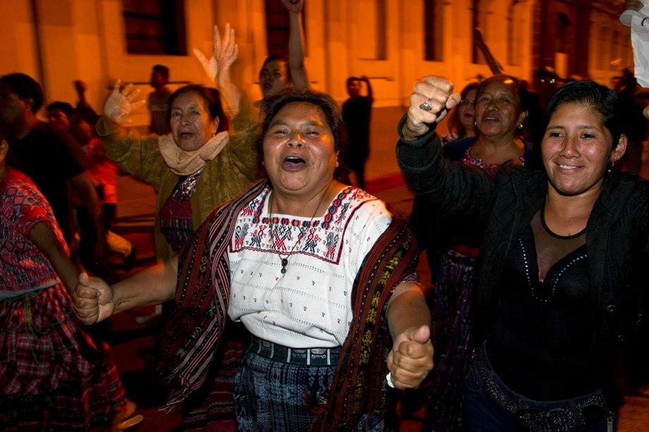 La gente festeja cerca del edificio del Congreso tras enterarse que la vicepresidenta guatemalteca Roxana Baldetti renunció tras un escándalo de corrupción en el que está implicado su exsecretario privado, en Ciudad de Guatemala, el viernes 8 de mayo de 2015. El presidente Otto Pérez Molina anunció el viernes que Baldetti dejará el puesto. (Foto AP/Moisés Castillo)