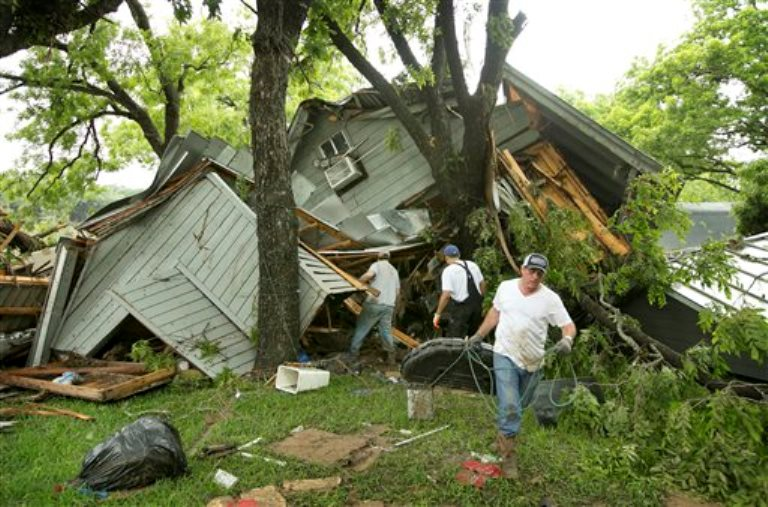 Jeremy Steele, izquierda, Ric Jaime, centro, y Keith McNabb rescatan pertenencias de la casa de su amigo Mike Cook cerca de Wimberley, Texas, el domingo, 24 de mayo del 2015. Lluvias récord causaron enormes daños en una sección del centro de Estados Unidos el domingo, con inundaciones en cuencas usualmente secas, desatando tornados y obligando a al menos 2.000 personas a abandonar sus hogares.(Jay Janner/Austin American-Statesman via AP)