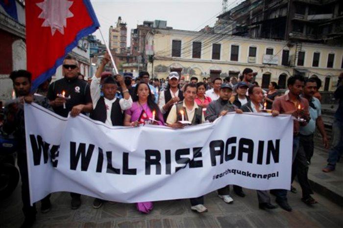 Un grupo de nepalíes rinde homenaje a las víctimas del potente terremoto del pasado 25 de abril que asoló el país, mientras caminan portando velas cerca de la detruida torre de Dharahar, en Katmandú, el 7 de mayo de 2015. El sismo mató a miles de personas y causó muchos más heridos al arrasar localidades de montaña y destruir edificios con siglos de historia en Katmandú. (Foto AP/Niranjan Shrestha)