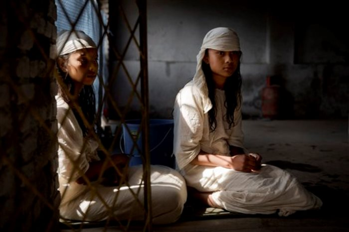 Las hermanas nepalíes Sushmita Pandit, de 16 años (a la izquierda), y Susha Pandit, de 14, que perdieron a su madre, una hermana y un hermano cuando su casa se vino abajo tras el terremoto del pasado 25 de abril, en un momento del 12mo día de su periodo de luto ritual, en Katmandú, Nepal, el 6 de mayo de 2015. El sismo del 25 de abril mató a miles de personas y dejó muchos más heridos al arrasar localidades de montaña y destruir edificios y monumentos en Katmandú. Las hermanas Pandit son de Sindhupalchok, uno de los distritos próximos al epicentro más afectados. (Foto AP/Bernat Armangue)