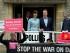 El primer ministro británico y líder del Partido Conservador, David Cameron, y su esposa Samantha a la salida de un centro de votación en Spelsbury, Inglaterra, mientras activistas protestan en la puerta, tras votar en las elecciones generales, el 7 de mayo de 2015. (Foto AP/Alastair Grant)
