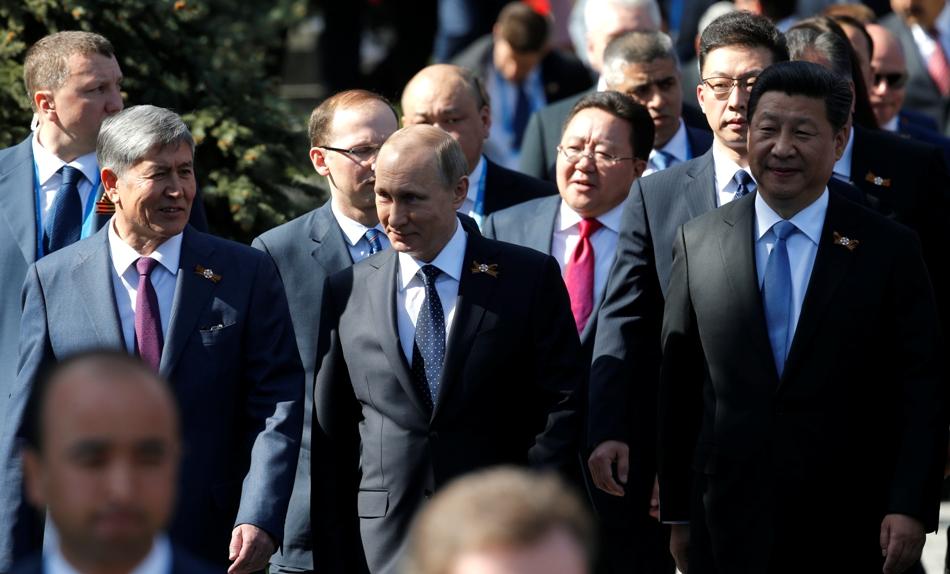 De izquierda a derecha: El presidente de Kirguistán, Almazbek Atambayev; el presidente de Rusia, Vladimir Putin; el presidente de China, Xi Jinping caminan antes del inicio del desfile de la Victoria para celebrar el 70 aniversario de la derrota de los nazis en la II Guerra Mundial, en la Plaza Roja de Moscú, el 9 de mayo de 2015. (Foto AP/Alexander Zemlianichenko, Pool)