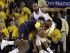 LeBron James, izquierda, pierde el equilibrio mientras se enfila al aro en contra de Andre Iguodala, de los Warriors de Golden State, durante acciones de tiempo extra del primer partido de la final de la NBA en Oakland, California, el jueves 4 de junio de 2015. (Foto AP/Ben Margot).