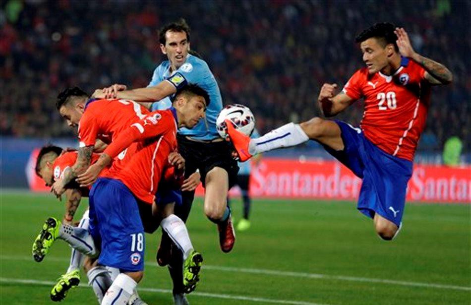 El jugador de Chile, Charles Aránguiza, derecha, salta para patear el balón en un partido contra Chile por los cuartos de final de la Copa América el miércoles, 24 de junio de 2015, en Santiago, Chile. (AP Photo/Ricardo Mazalan)
