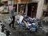 En esta imagen del 10 de junio de 2015, civiles inspeccionan el lugar de un atentado con coche bomba en la Calle Palestina al este de Bagdad, Irak.  (Foto AP/Karim Kadim, Archivo)