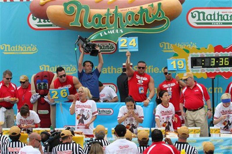 """Miki Sudo, 2da izquierda, y Sonya """"Viuda Negra"""" Thomas, centro, participan en el concurso de comer hot dogs en la playa neoyorquina de Coney Island, parte de los festejos tradicionales del Día de la Independencia de Estados Unidos, sábado 4 de julio de 2015. Sudo se impuso con 38 salchichas.  (AP Foto/Tina Fineberg)"""