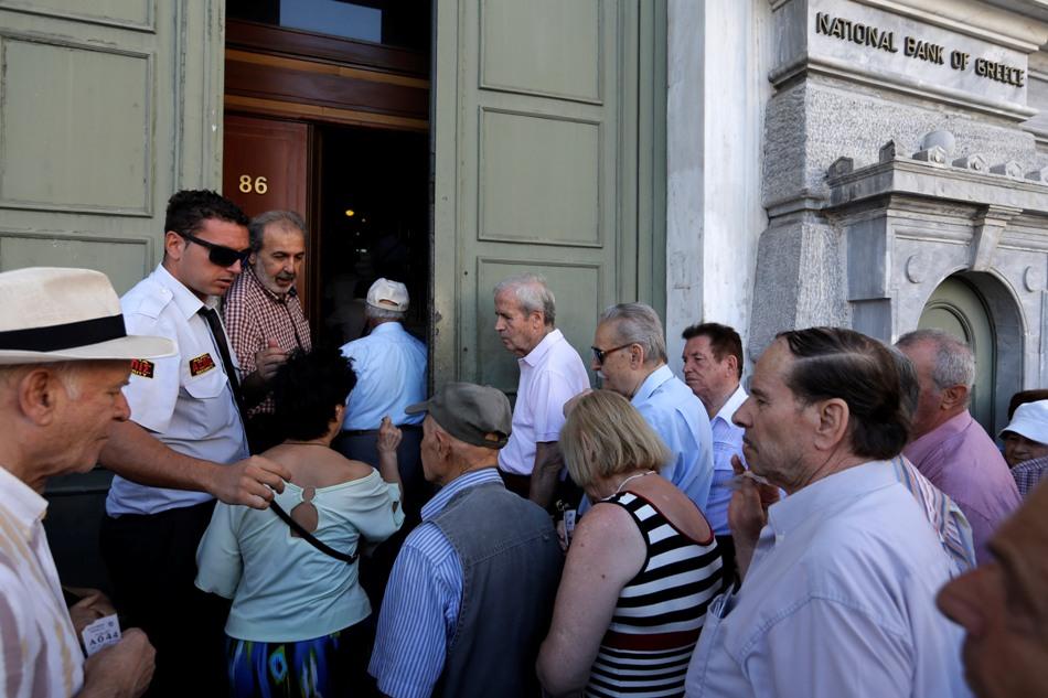 Los primeros clientes, la mayoría pensionistas, entran en una sucursal en la sede del Banco Nacional de Grecia en Atenas, el lunes 20 de julio de 2015. Los griegos se despertaron el lunes por la mañana en un nuevo mundo: los bancos abrían de nuevo tras tres semanas cerrados, pero los nuevos impuestos hacían encarecido el café, el té e incluso los preservativos. (AP Foto/Thanassis Stavrakis)