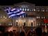 """Una mujer ondea una bandera griega durante los festejos tras el triunfo del """"No"""" en el referendo convocado por el gobierno de Grecia, en la Plaza Syntagma frente al Parlamento en Atenas, el domingo 5 de julio de 2015. (Foto AP/Emilio Morenatti)"""