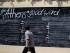 Un peatón mira una pizarra donde la gente puede escribir sus comentarios sobre la capital griega, en un muro de Atenas, el lunes 27 de julio de 2015.. (AP Foto/Thanassis Stavrakis)
