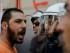 """Un sindicalista comunista vocifera consignas frente a la policía durante una protesta contra la austeridad y a favor del voto por el """"no"""" en el centro de Atenas, el viernes 3 de julio de 2015. (AP Foto/Petros Karadjias)"""