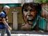 Un hombre pasa junto a un grafiti en Atenas, el martes 21 de julio de 2015. Los bancos reabrieron el lunes por primera vez en tres semanas. Pero para la mayoría de los griegos, asfixiados por seis años de recesión, lo importante era el aumento de los precios tras la subida del IVA reclamada por los acreedores del país. (AP Foto/Thanassis Stavrakis)