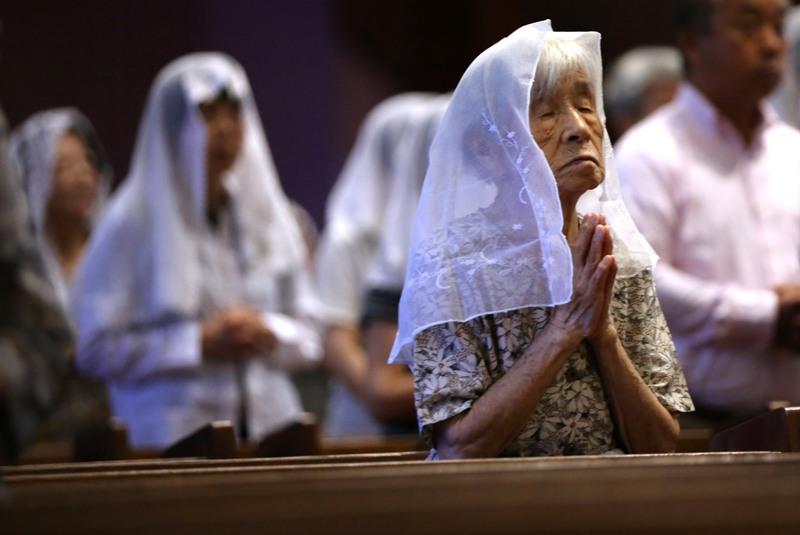 Católicos rezan durante una misa en recuerdo de las víctimas de la bomba atómica, el domingo 9 de agosto de 2015, en la catedral de Urakami, en la ciudad japonesa de Nagasaki, al cumplirse el 70 aniversario de la bomba lanzada por Estados Unidos que mató a más de 70.000 personas. (Foto AP/Eugene Hoshiko)