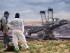 Manifestantes observan una excavadora en una mina de carbón a cielo abierto en Garzweiler, Alemania, sábado 15 de agosto de 2015. Manifestantes ambientalistas irrumpieron en una mina de lignito en el oeste de Alemania en protesta contra el uso de carbón, una gran fuente de gases de invernadero. ( Marius Becker/dpa via AP)