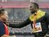 El jamaiquino Usain Bolt, derecha, recibe un regalo del camarógrafo que lo derribó en un vehículo personal de dos ruedas el jueves 27 de agosto, durante la ceremonia de premiación de los 200 metros del Mundial de Atletismo el viernes, 28 de agosto de 2015, en Beijing. (AP Photo/Kin Cheung)