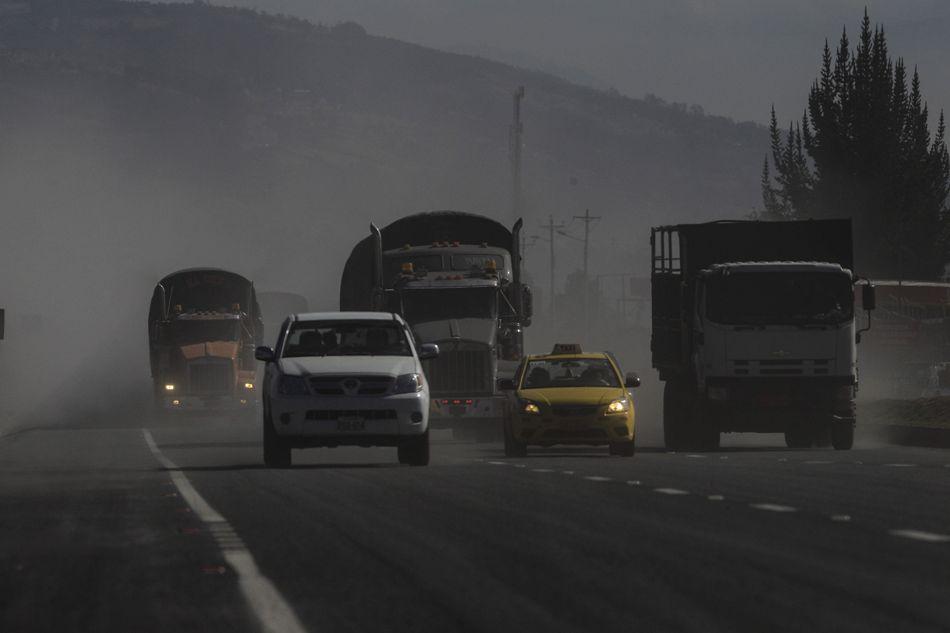 Vehículos levantan la ceniza caída en la carretera Panamericana a su paso en la población de Machachi (Ecuador), tras las dos explosiones freáticas que se registraron en la madrugada de hoy, viernes 14 de agosto de 2015, en el volcán Cotopaxi, en el centro andino del país. EFE/José Jácome