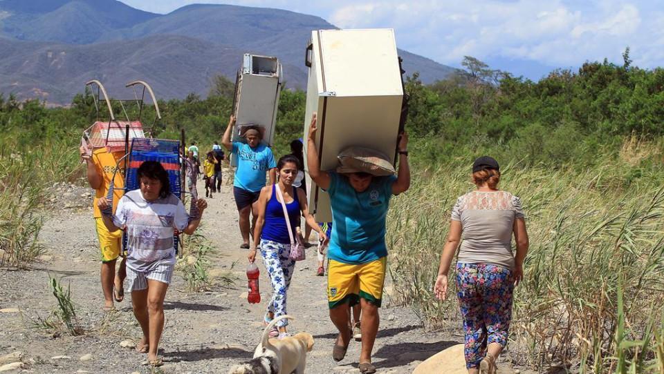 Colombianos cargan sus pertenencias por el río Táchira desde Venezuela hacia el sector La Parada (Colombia) el martes 25 de agosto de 2015, en Cúcuta (Colombia). EFE/Mauricio Dueñas Castañeda
