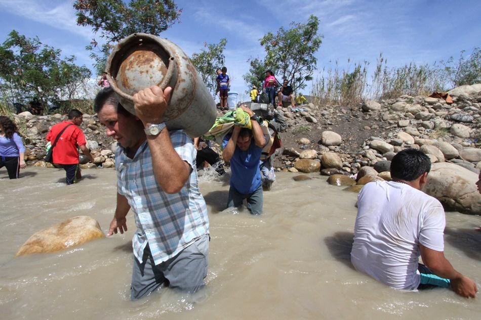 Personas transportan sus pertenencias através del fronterizo río Táchira desde San Antonio del Táchira, Venezuela, hacia territorio colombiano, el martes 25 de agosto de 2015. .(AP Photo/Eliecer Mantilla)