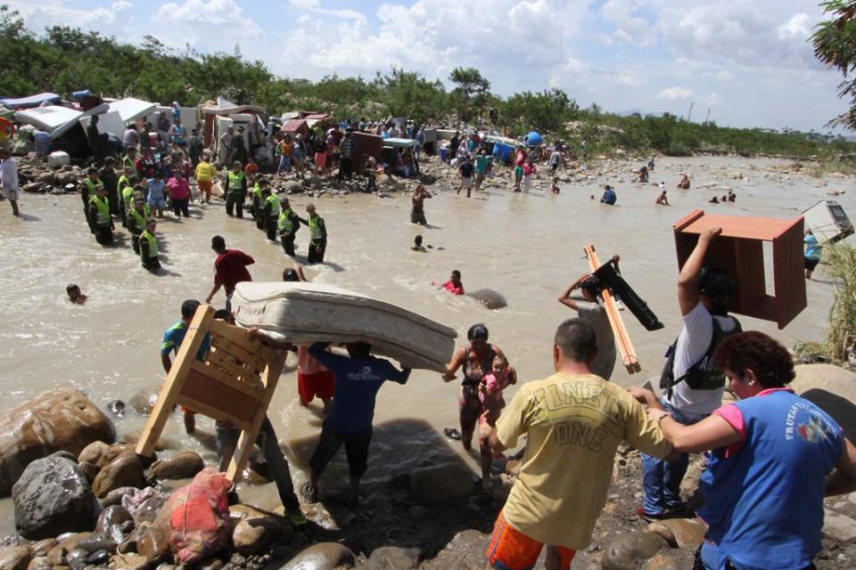 Colombianos cargan sus pertenencias a traés del río Táchira de regreso a su país el martes 25 de agosto de 2015 en medio de la expulsión masiva de ciudadanos de ese país de Venezuela. (Foto AP/Eliecer Mantilla)