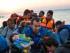Un hombre lleva una niña en brazos mientras migrantes llegan a la costa en una lancha neumática procedente de la costa turca, en la costa de la isla griega de Kos, en el mar Egeo, al amanecer del 13 de agosto de 2015. (Foto AP/Alexander Zemlianichenko)