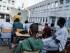 En esta imagen, tomada el 6 de agosto de 2015, Camille Arrignon, una francesa de 23 años, da clase de francés a migrantes en el patio de la escuela secundaria Guillaume-Bude de Paris. Por el momento, París hace la vista gorda y permite que asociaciones conviertan algunos edificios públicos vacíos en alberges de emergencia, como esta escuela que cobija a unos 200 migrantes. (Foto AP/Kamil Zihnioglu)
