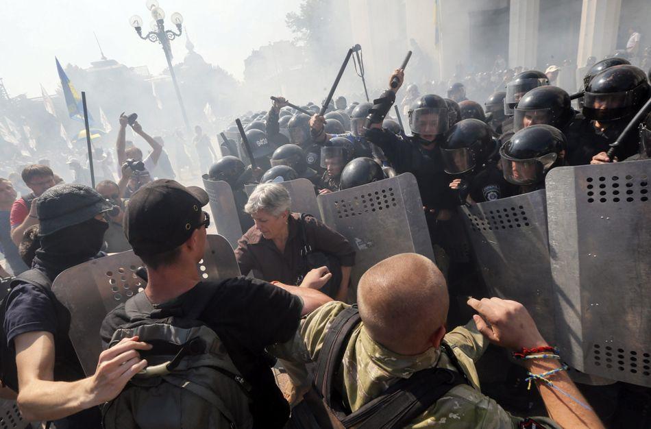 Opositores de la reforma constitucional se enfrentan a la policía ante el Parlamento ucraniano en Kiev (Ucrania) hoy, 31 de agosto de 2015. Una veintena de militares y una decena de policías resultaron heridos hoy a consecuencia de una explosión junto a la sede del Parlamento de Ucrania durante enfrentamientos entre las fuerza de seguridad y un grupo de manifestantes radicales, informaron las autoridades. Los radicales, según medios locales, lanzaron un artefacto explosivo contra el cordón policial que custodiaba el Parlamento poco después de que el Legislativo aprobara una reforma constitucional para descentralizar el país. EFE/Sergey Dolzhenko
