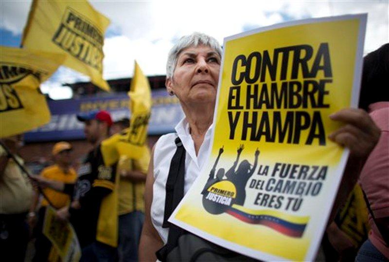 Una mujer sostiene un cartel durante una manifestación pacífica contra el hambre y la delincuencia, en Caracas, Venezuela, el sábado 8 de agosto de 2015. La manifestación opositora se dio en medio de las tensiones generadas por algunos casos de saqueos de comercios. (AP Photo/Ariana Cubillos)
